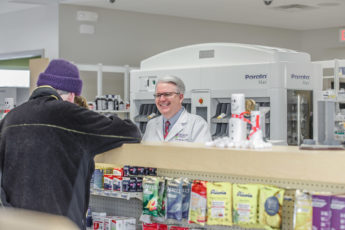 John Forbes with a customer at Medicap Pharmacy