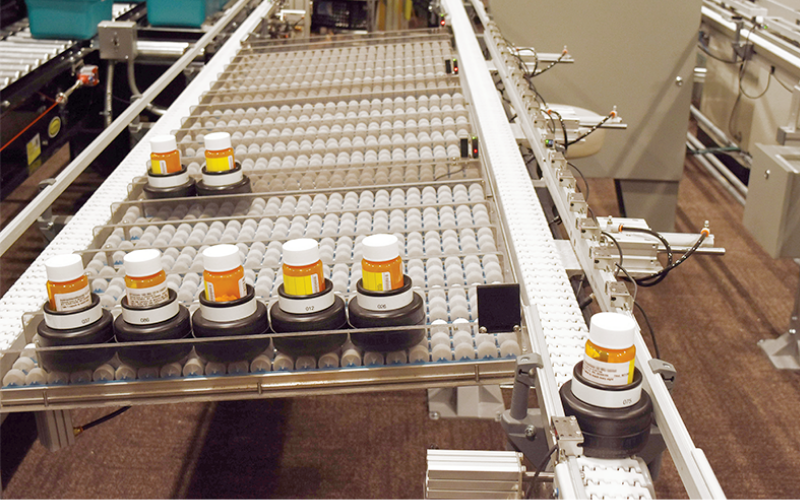 completed vials are transported and sorted in pucks on the conveyor at a central fill pharmacy